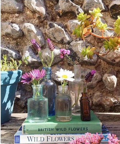 Styling foraged finds from a walk using single stemmed flowers in individual vases