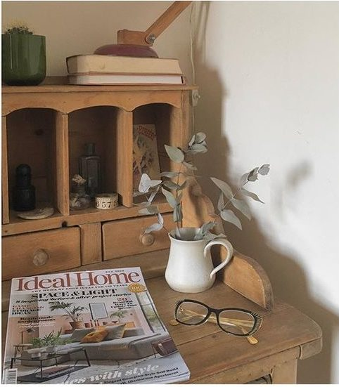 We love interiors magazines! Lifestyle image of a wooden dresser with a collection of items.