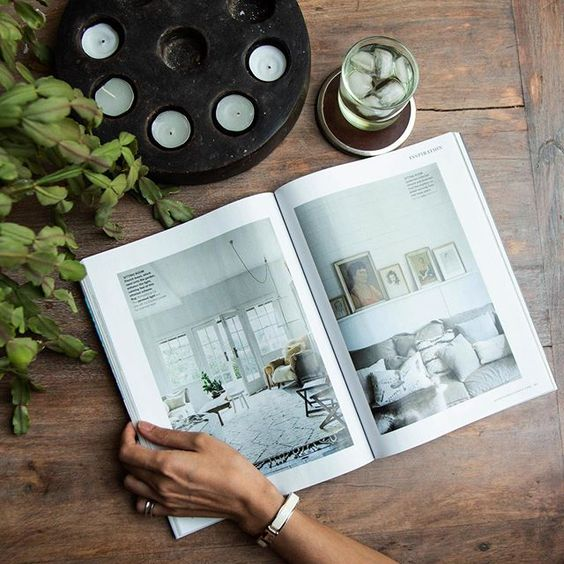 We love interior magazines! Flat lay of a magazine and glass of water.