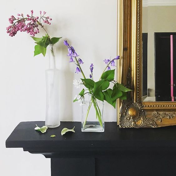 Styling foraged finds. Single stemmed flowers in glass vases on a mantlepiece.