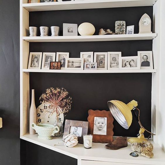 20 of the best vintage interiors in the UK. Styled white shelves with vintage photo frames