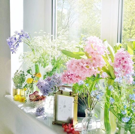 How to use colour in a room. Window sill with colourful flowers displayed in glass vases