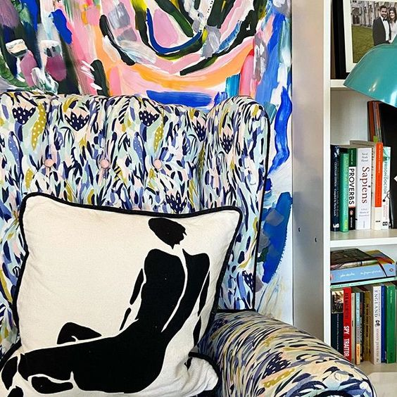 How to use colour in a room. Reading chair with a bold blue pattern and monochrome cushion with a black silhouette