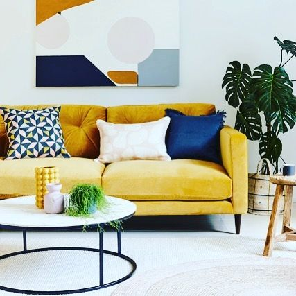 How to use colour in a room. Bright yellow sofa styled with colourful blue cushions