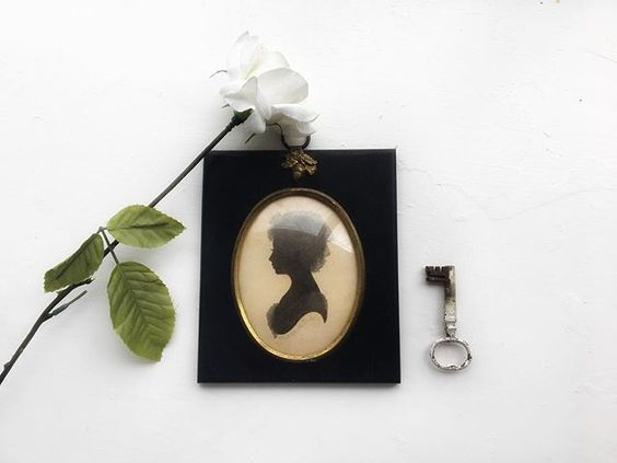 The secret styling tip for adding personality to your home that you need to know! Flat lay of a portrait with a single stem flower and vintage key
