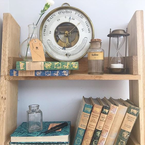 20 of the best vintage interiors in the UK. Vintage colourful books and a weather gauge on open shelving