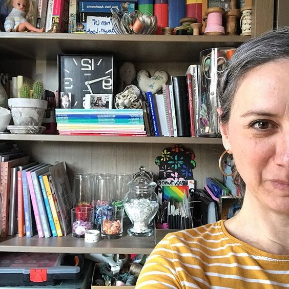 The secret styling tip for adding personality to your home that you need to know! Woman sitting in front of open shelves with a collection of books