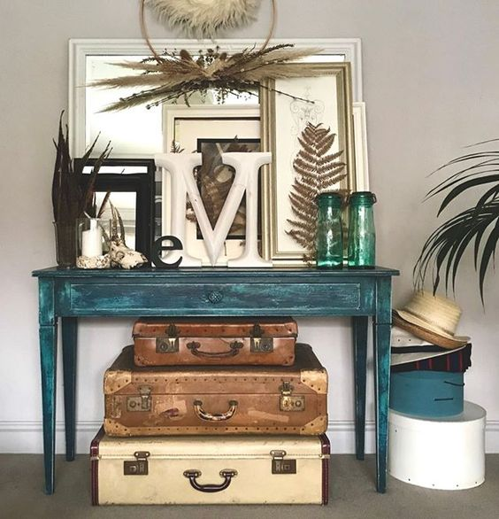 20 of the best vintage interiors in the UK. A collection of vintage suitcases underneath a turquoise vintage table