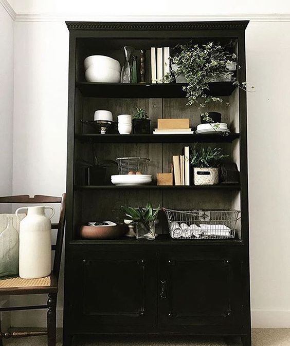 The secret styling tip for adding personality to your home that you need to know! Black dresser with lifestyle items such as books and vases