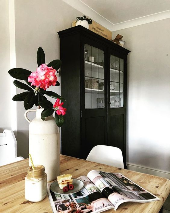 How to use colour in a room. Beautiful pink flowers styled in front of a black dresser