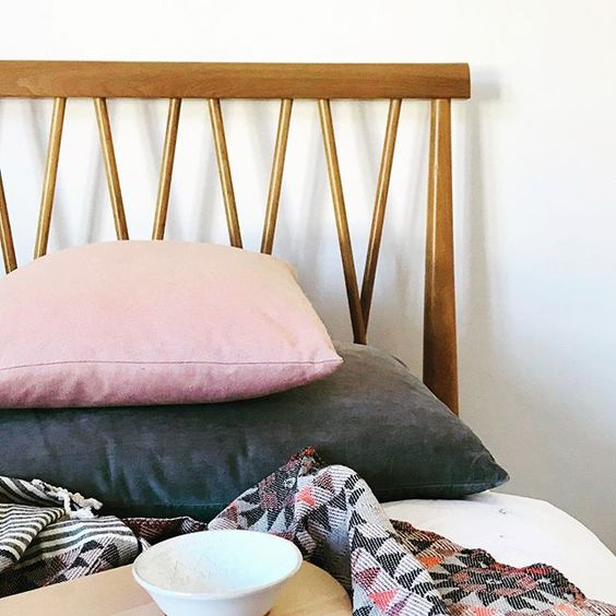 How to use colour in a room. Mid-century modern bed frame with blush pink and dark grey cushions