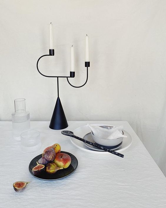 The secret styling tip for adding personality to your home that you need to know! Lifestyle vignette of a black, sculptural candlestick and cut figs