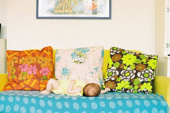 The secret styling tip for adding personality to your home that you need to know! Baby asleep on a sofa with 3 colourful, floral cushions