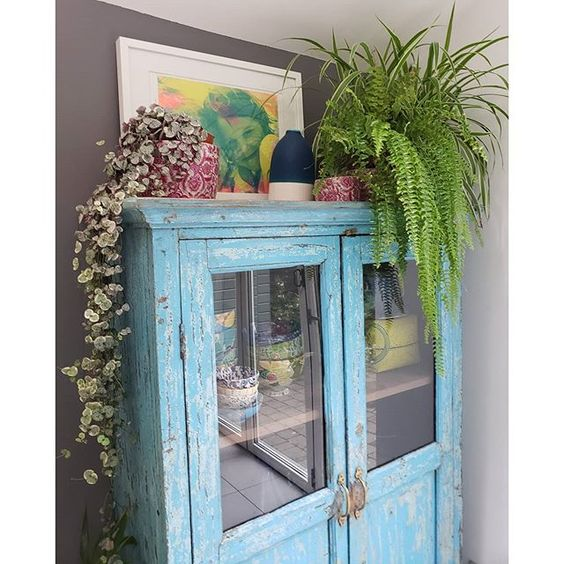 20 of the best vintage interiors in the UK. Vintage blue dresser with vintage crockery and plants
