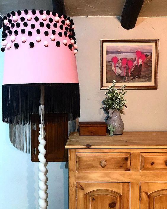 How to use colour in a room. Pink lampshade with black pompoms next to a bedroom dresser