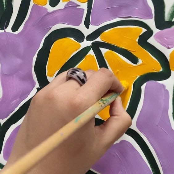 19 creative ways to use paper. Image of a hand painting a yellow flower.