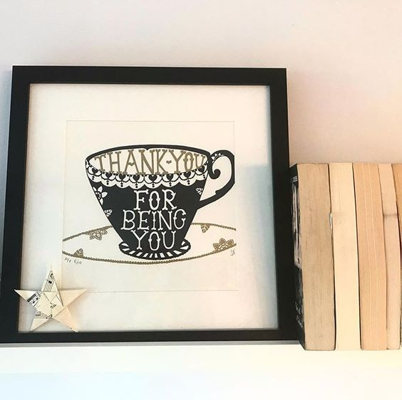 19 creative ways to use paper. Lifestyle shot of a shelf containing books, an art print and a paper star