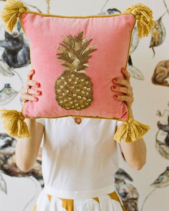 How to stay positive online in 2020. Lady hiding behind a pink cushion with a gold pineapple