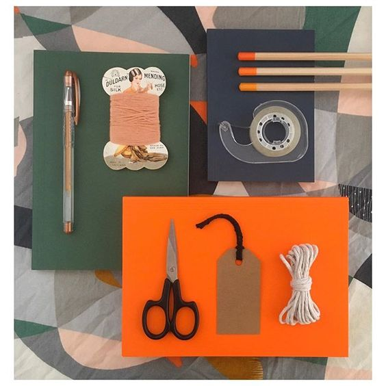 19 creative ways to use paper.Colourful lifestyle flat lay containing green and orange items, such as scissors, sellotape and matches.