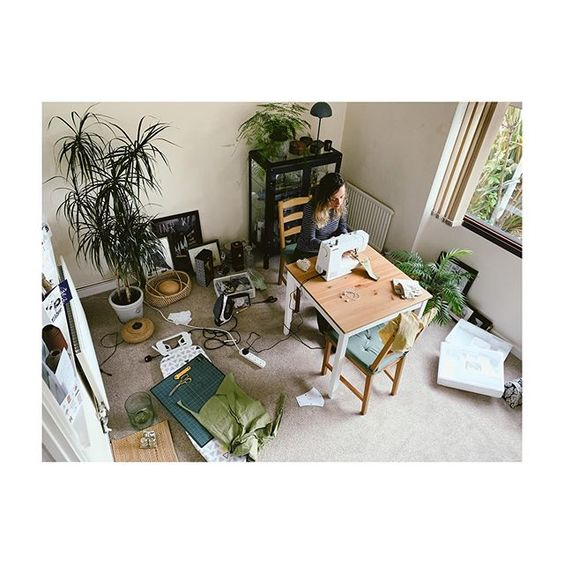 How to stay positive online in 2020. Birdseye shot of a room with a lady sewing at a table and green plants.