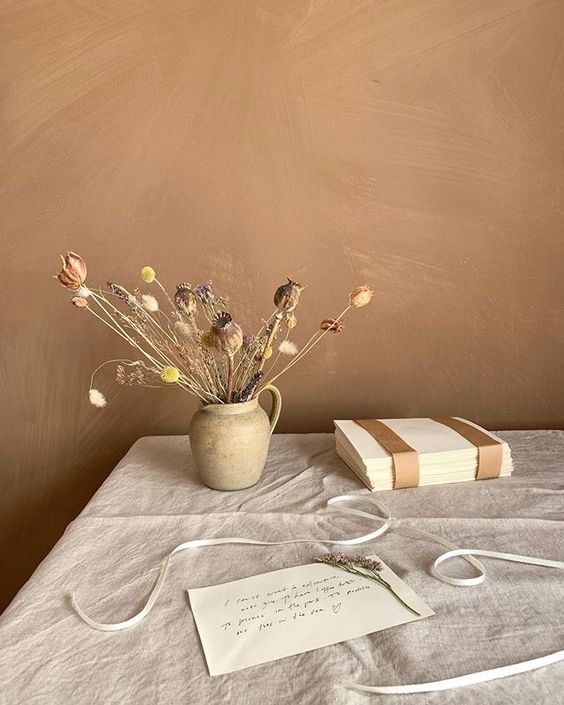 19 creative ways to use paper. Lifestyle still life of paper, a wrapped book and some dried flowers styled on a linen tablecloth