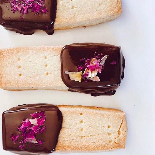 Food styling with shortbread biscuits dipped in chocolate with rose petals