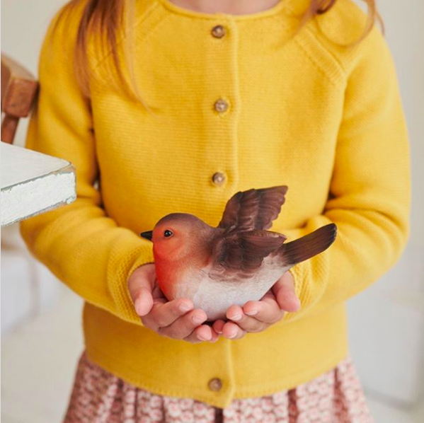 Picture of a child wearing a yellow cardigan holding a toy robin in her hands.