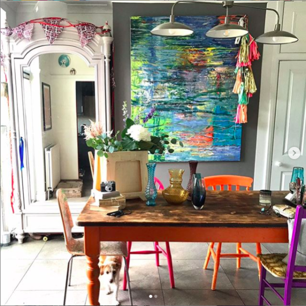 Colourful dining room with brightly painted chairs and artwork