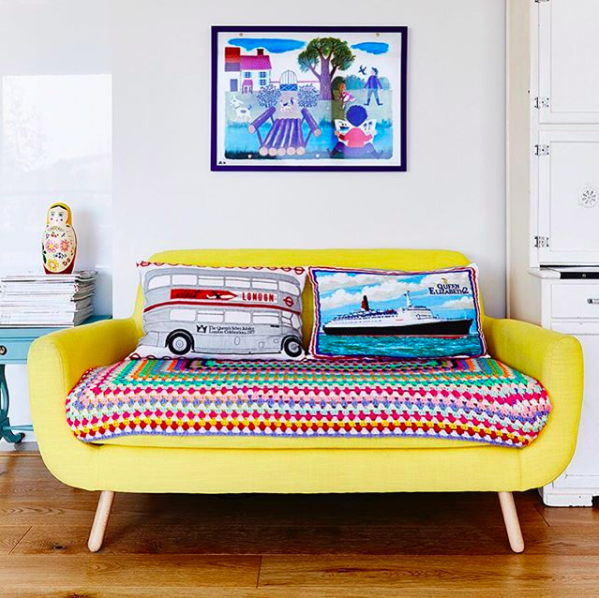 Brightly coloured yellow sofa styled in front of a colourful piece of wall art and with a brightly coloured throw and pillows.