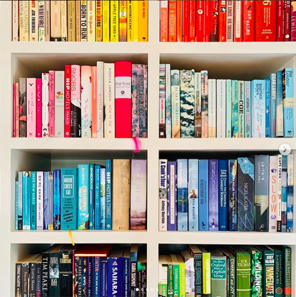 Set of colourful bookshelves with books arranged by colour of their spine.