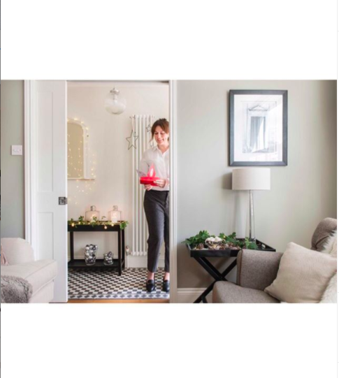 Interior styling shot of a woman holding a Christmas gift in a beautifully styled home