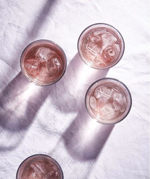 Birds eye view of a still life image of 3 glass tumblers filled with pink juice.