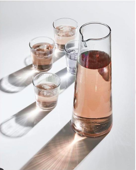 Lifestyle shot of a glass jug and water glasses with pink liquid