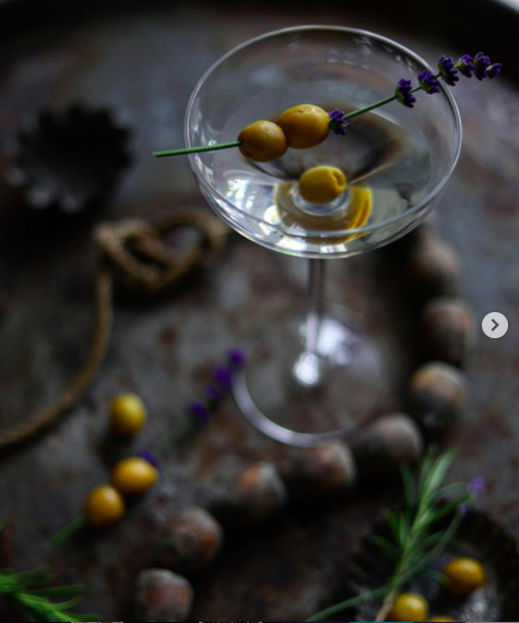 Lifestyle image of a martini glass with green olives