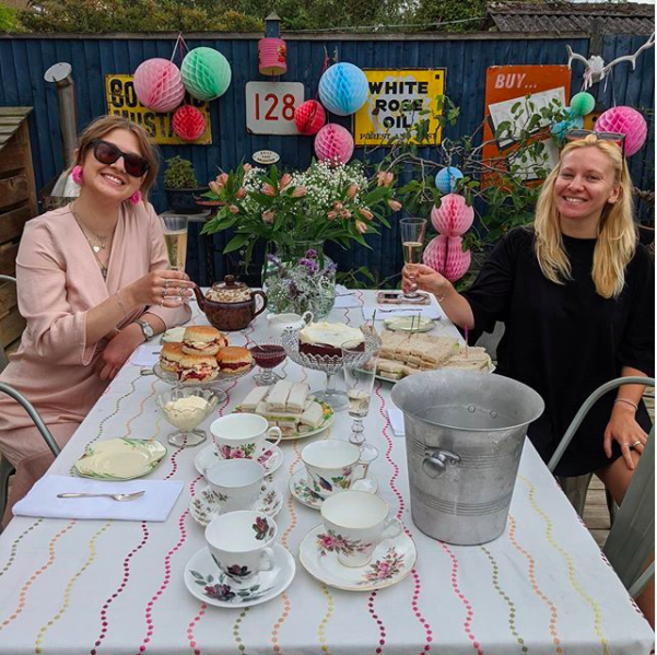 My happy place. Shot of two ladies raising a glass at an outdoor party styled with colourful pom poms and a table of afternoon tea.
