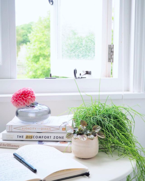My happy place. A shot of an open window styled with some books and a plant pot in front of it.