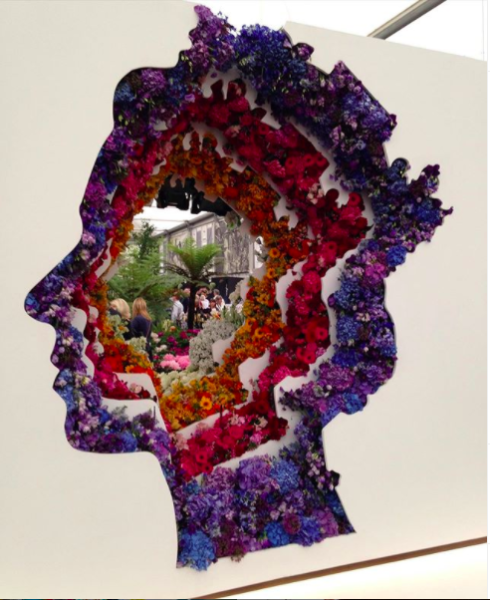 Floral art installation of brightly coloured flowers creating the Queen's head