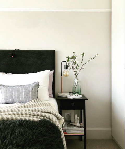 My happy place. Shot of a styled bed with a dark headboard and layered bedding.