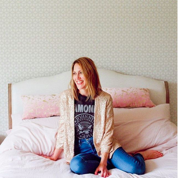 My happy place. A woman sitting on a bed wearing casual clothes and smiling.
