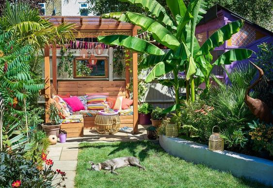 My happy place. Colourful garden with homemade wooden seating and colourful scatter cushions.