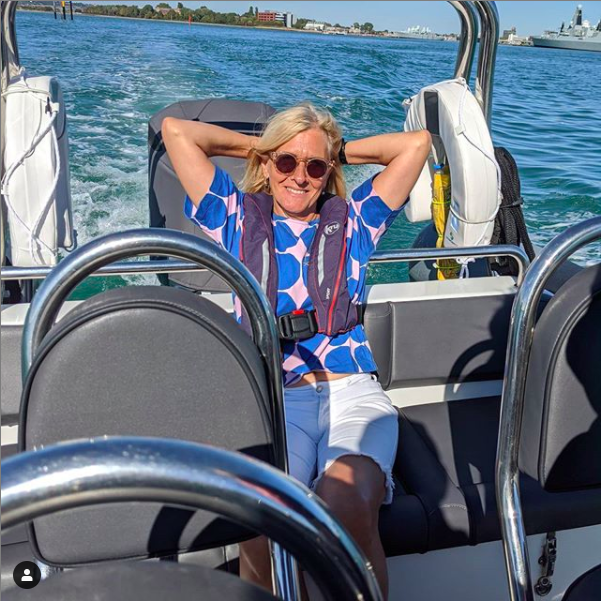 Photograph of a woman wearing sunglasses sitting on a speed boat in the summer sunshine.