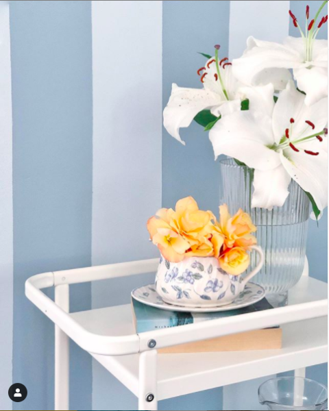 Beautifully styled table next to pastel blue striped wallpaper