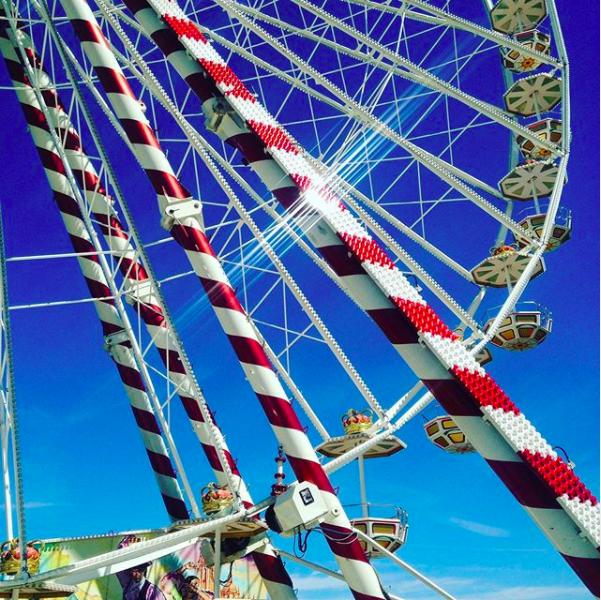 Brightly coloured summer fair ferris wheel in the sunlight